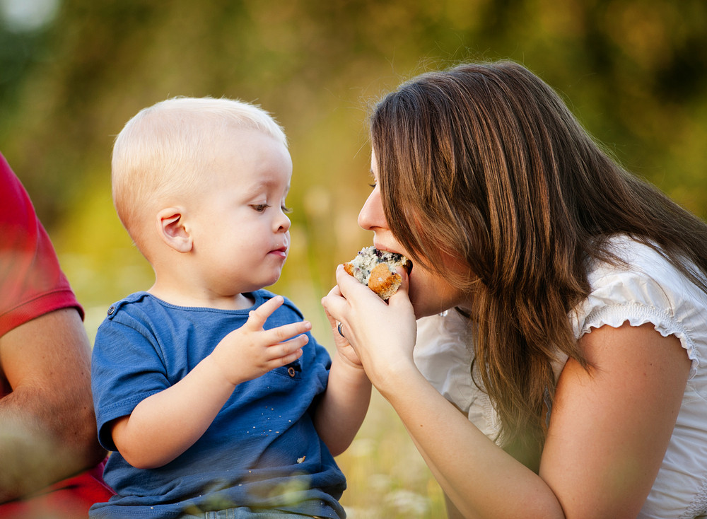 Cute little boy is feeding mother with muffin cake in nature