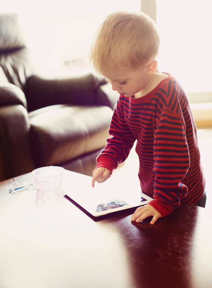 Cute little boy is playing on tablet at home
