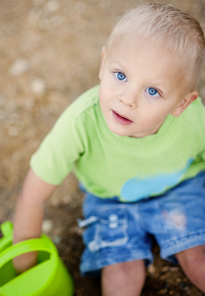 Cute little boy playing with the sand outside
