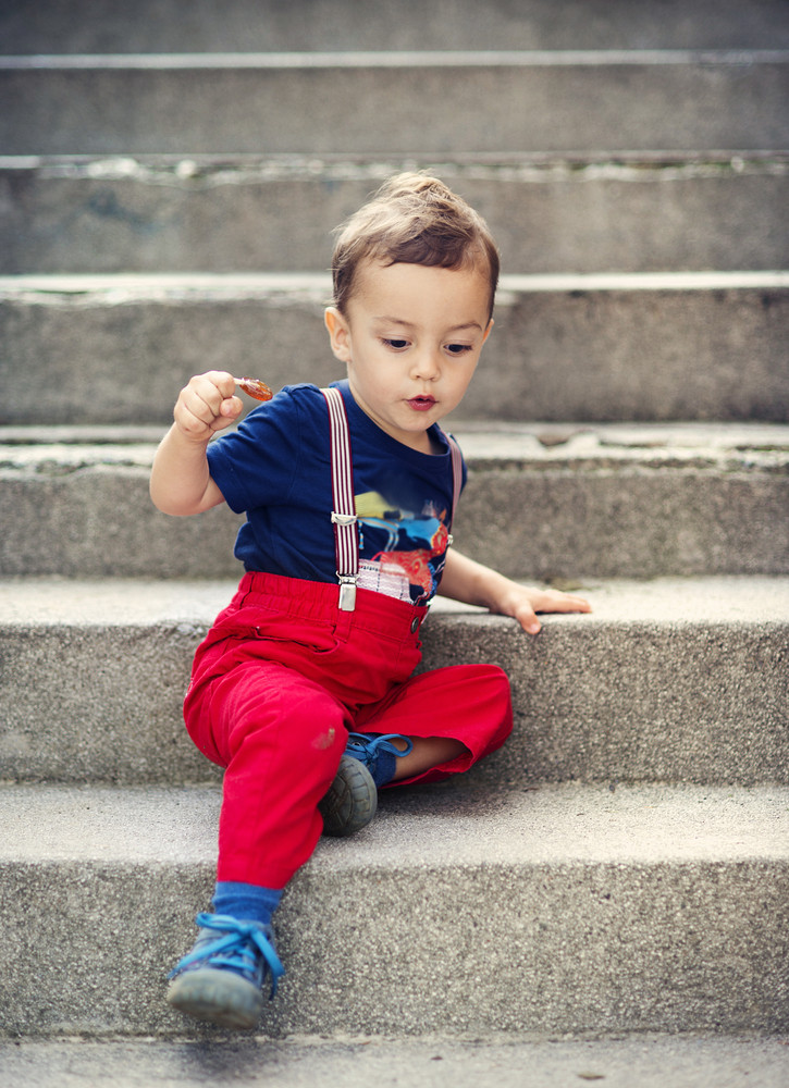 Cute little boy sitting on stairs during a summer day