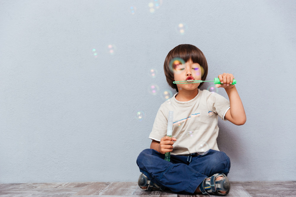 Cute little boy sitting with legs crossed and blowing soap bubbles over gray background