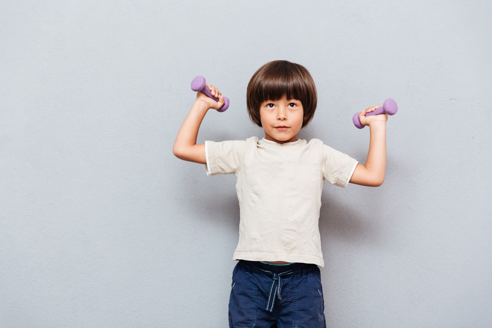 Cute little boy standing and working out with dumbbells over gray background