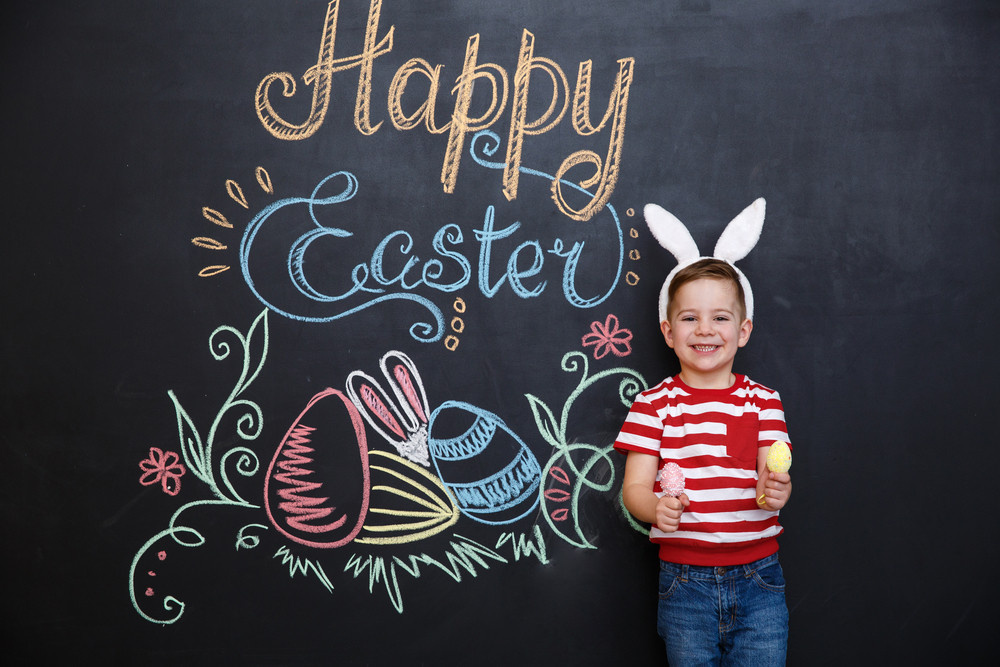 Cute little boy wearing rabbit ears and holding two eggs while standing inside big cracked eggshell over chalk board with easter doodles background
