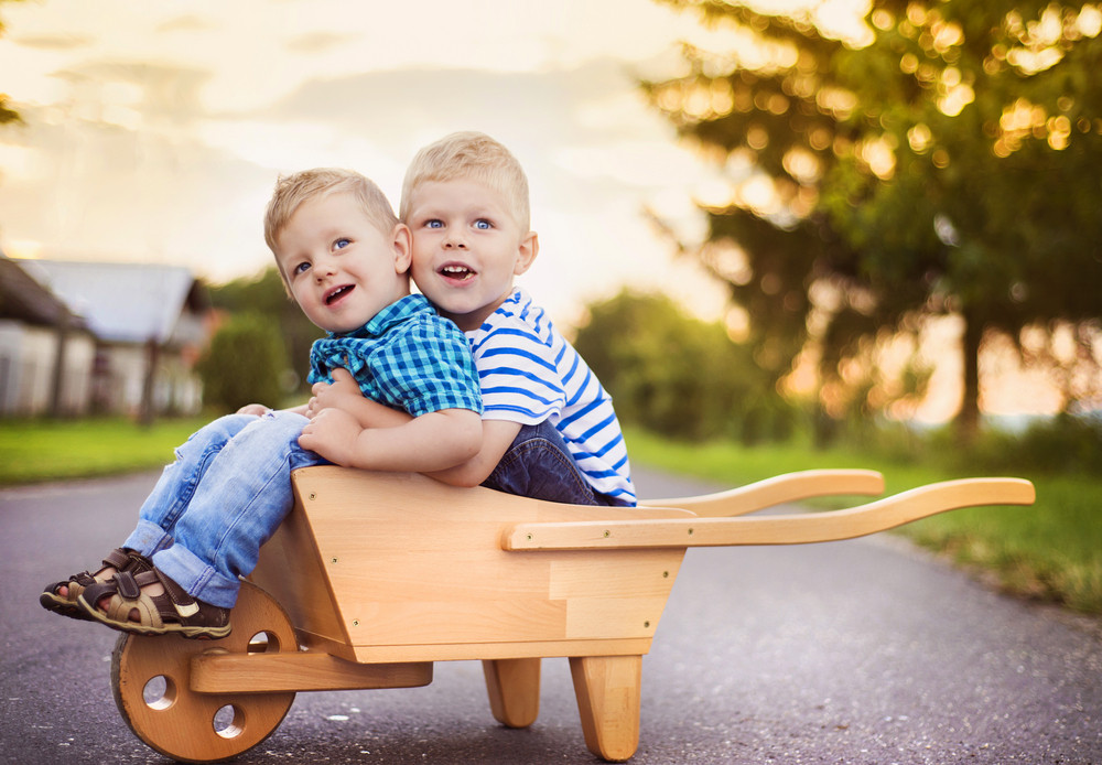 Cute little boys playing and having fun outside on a street