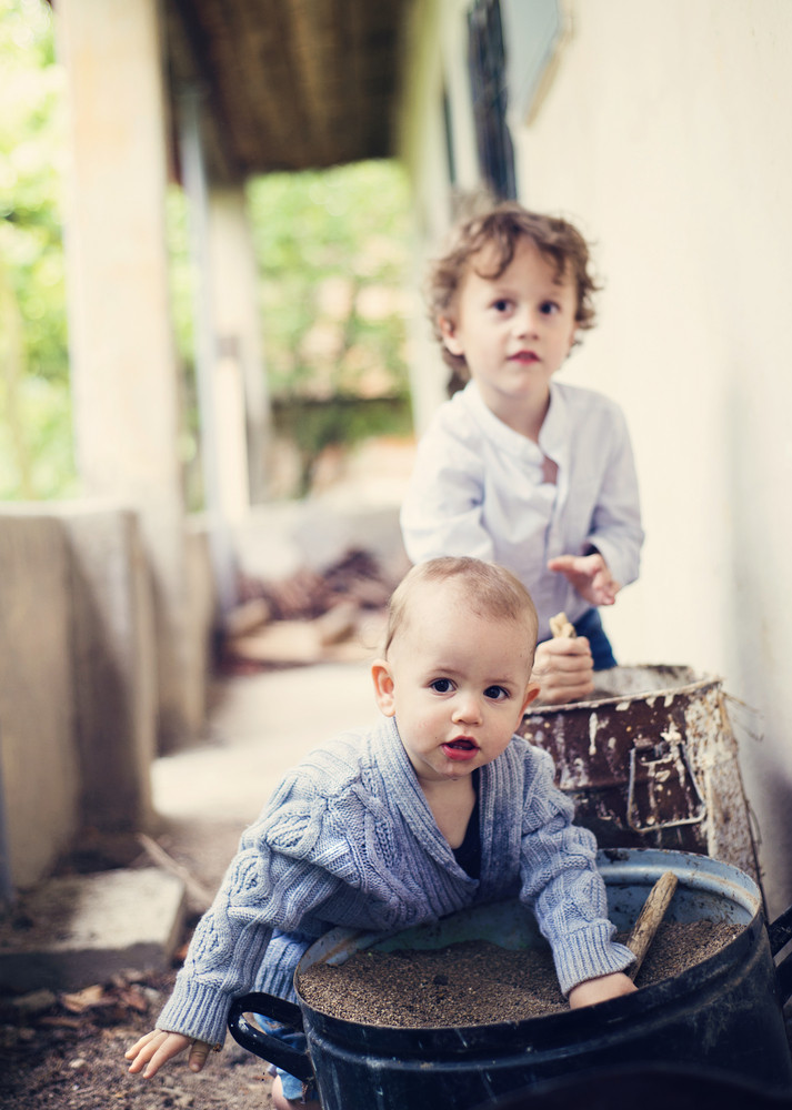 Cute little boys playing and having fun outside the house