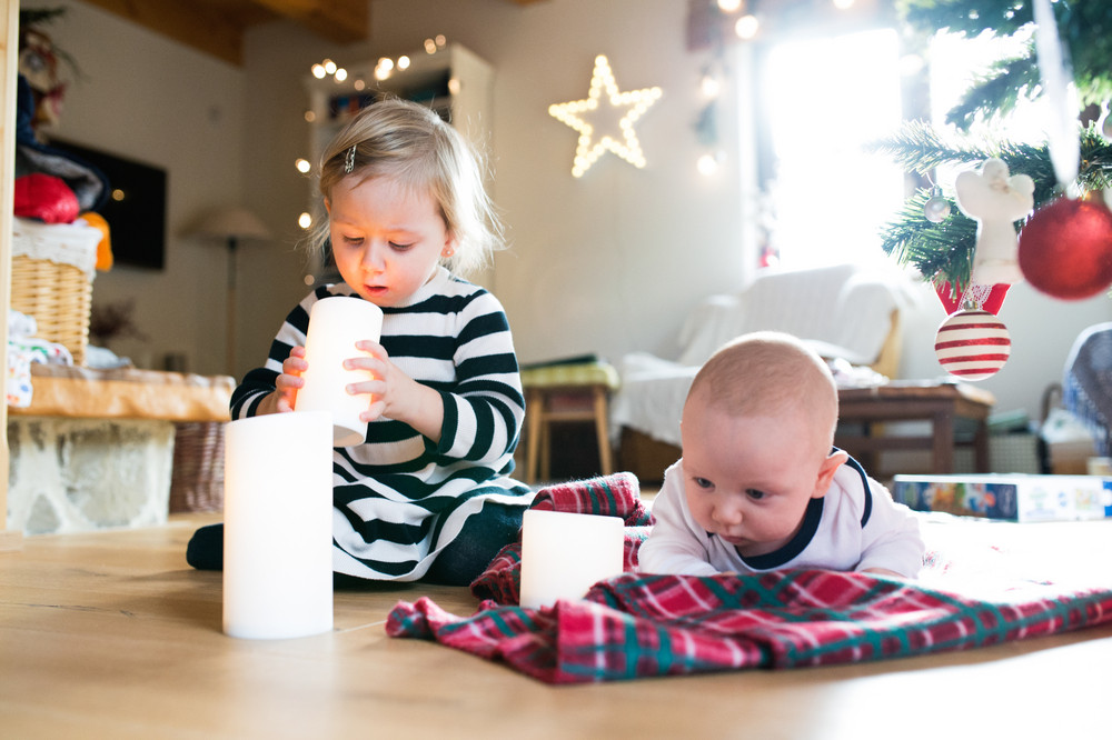Cute little children under the Christmas tree, girl playing with candles