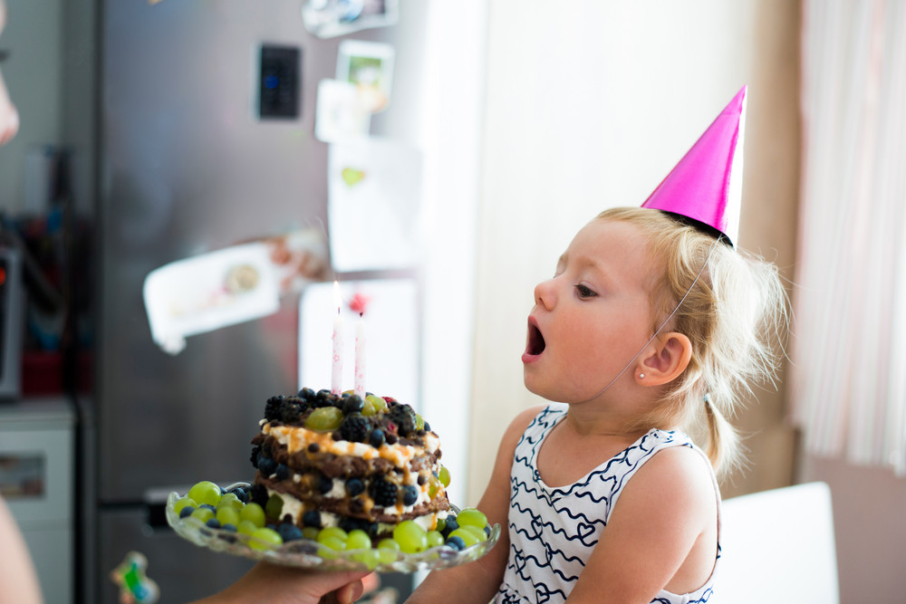 Cute Little Girl Blowing Candles On Her Fruit Birthday Cake Pink Party Hat Head