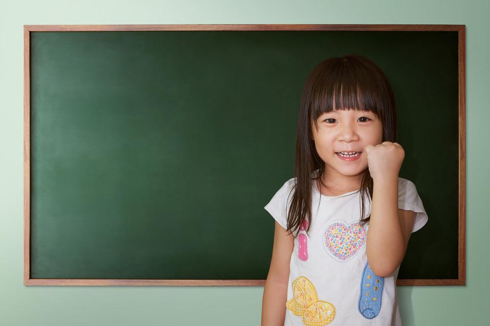 Cute little girl cheering on a background of black school board
