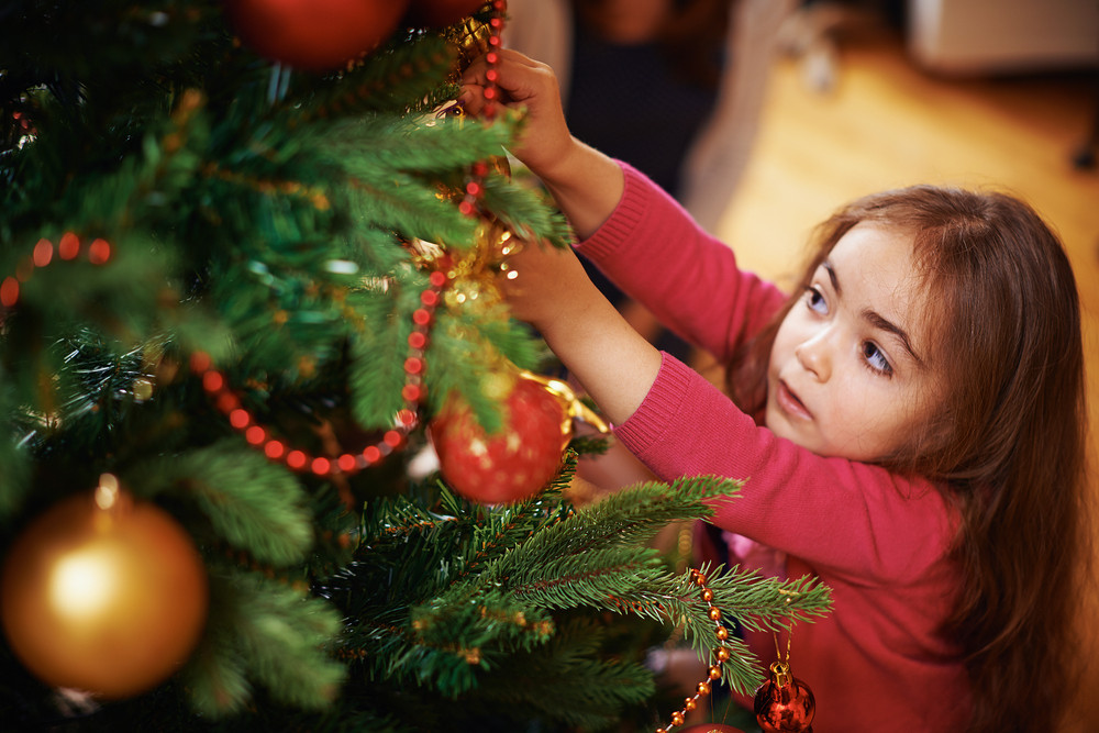 Cute Little Girl Decorating Christmas Tree Royalty-Free