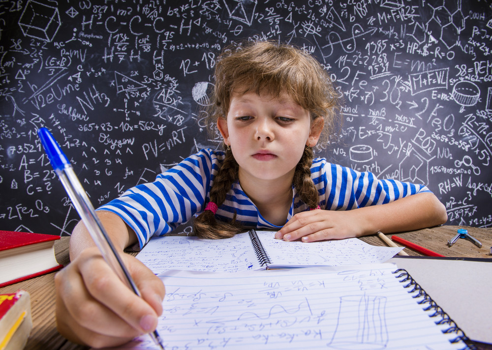 Cute little girl doing her homework in front of big blackboard