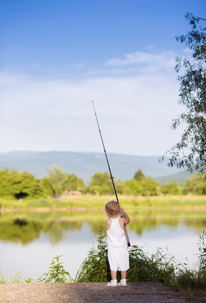 Cute little girl fishing on the lake with