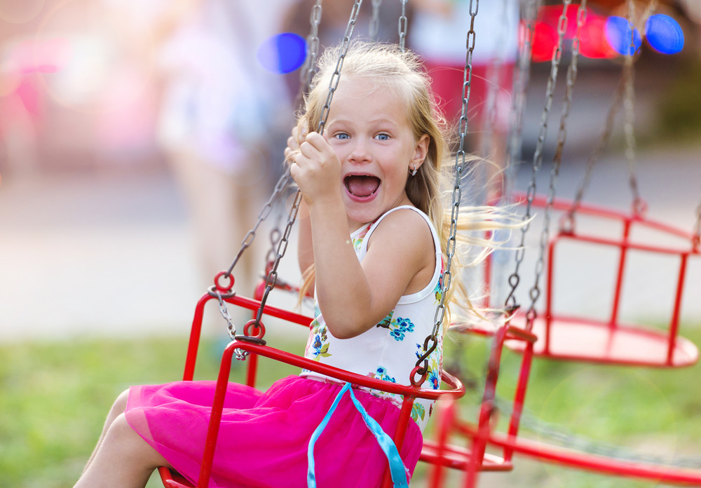 Cute little girl having fun at fun fair