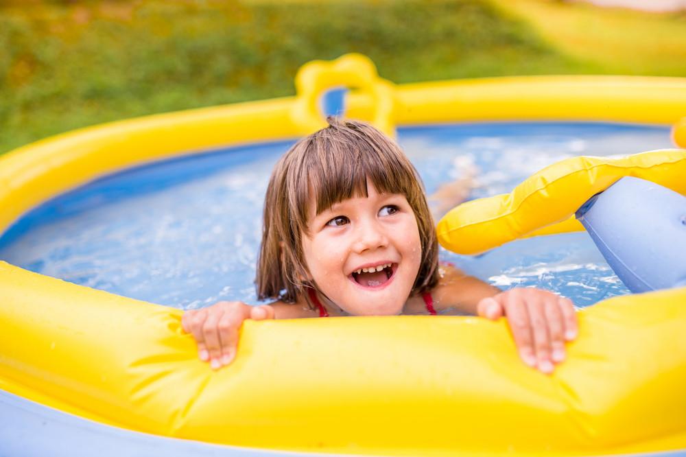 Cute little girl having fun in yellow garden swimming pool. Sunny summer day at the backyard