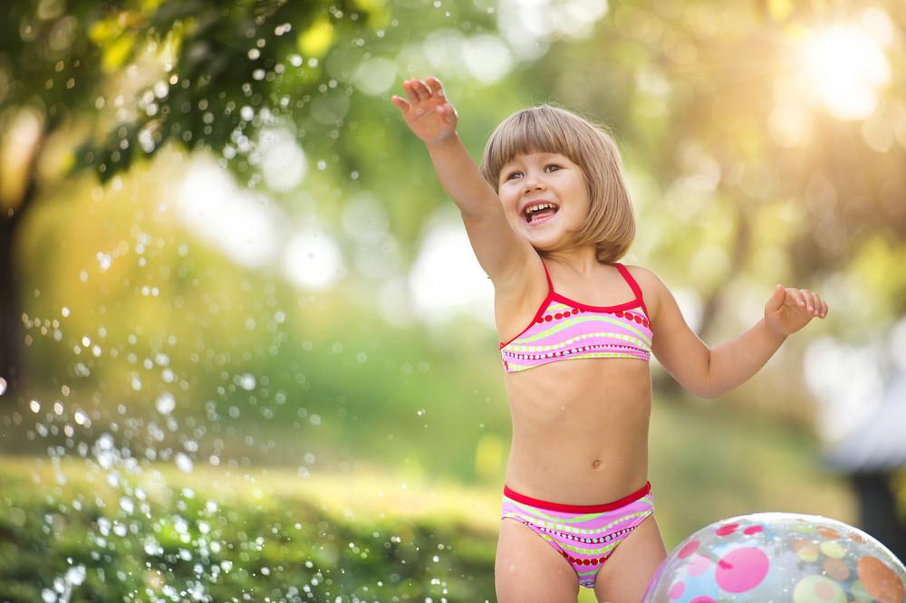 Cute little girl having fun outside in summer garden