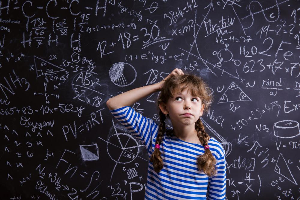 Cute little girl in front of big blackboard