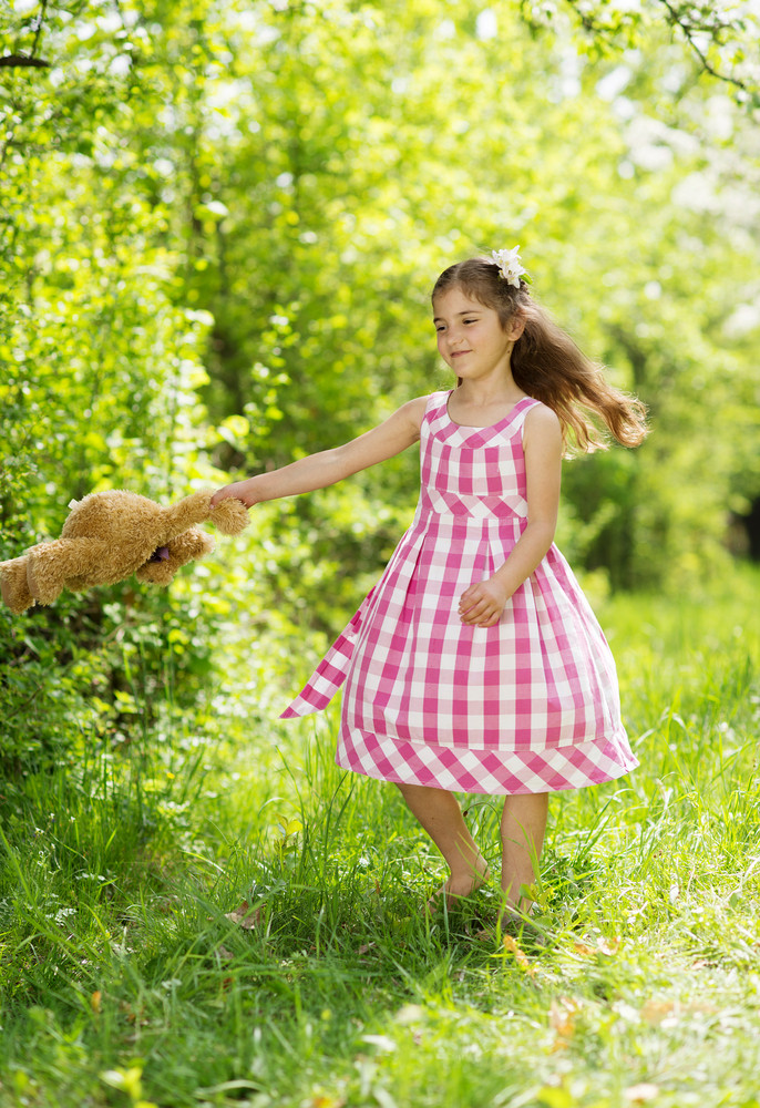 Cute little girl in pink dress is playing with brown teddy in green nature