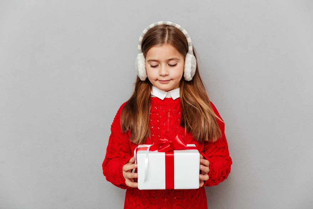 Cute little girl in red sweater and earmuffs standing and holding gift box