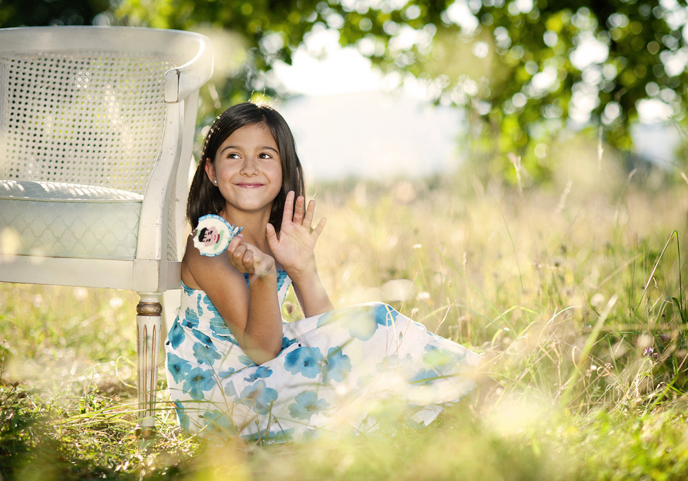 Cute little girl is enjoying leisure time with lollipop in green sunny park
