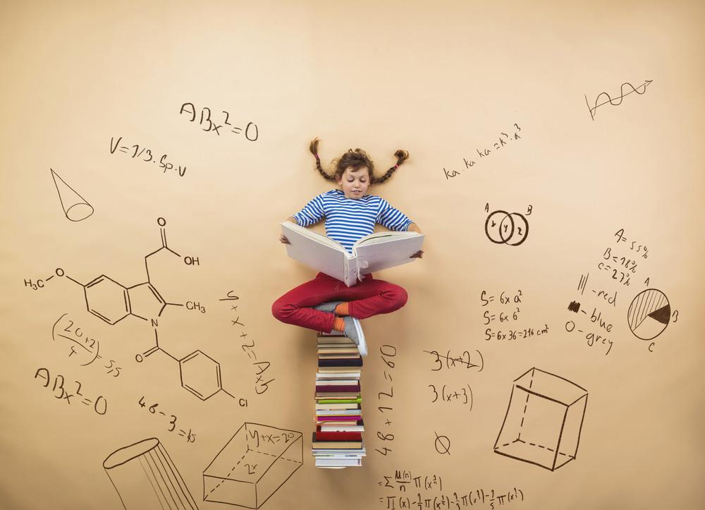 Cute little girl learning playfully in frot of a big blackboard. Studio shot on beige background.
