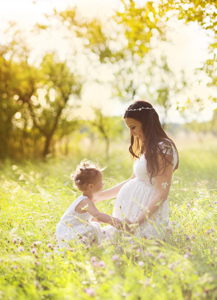 Cute little girl touching her mother's pregnant belly in summer nature