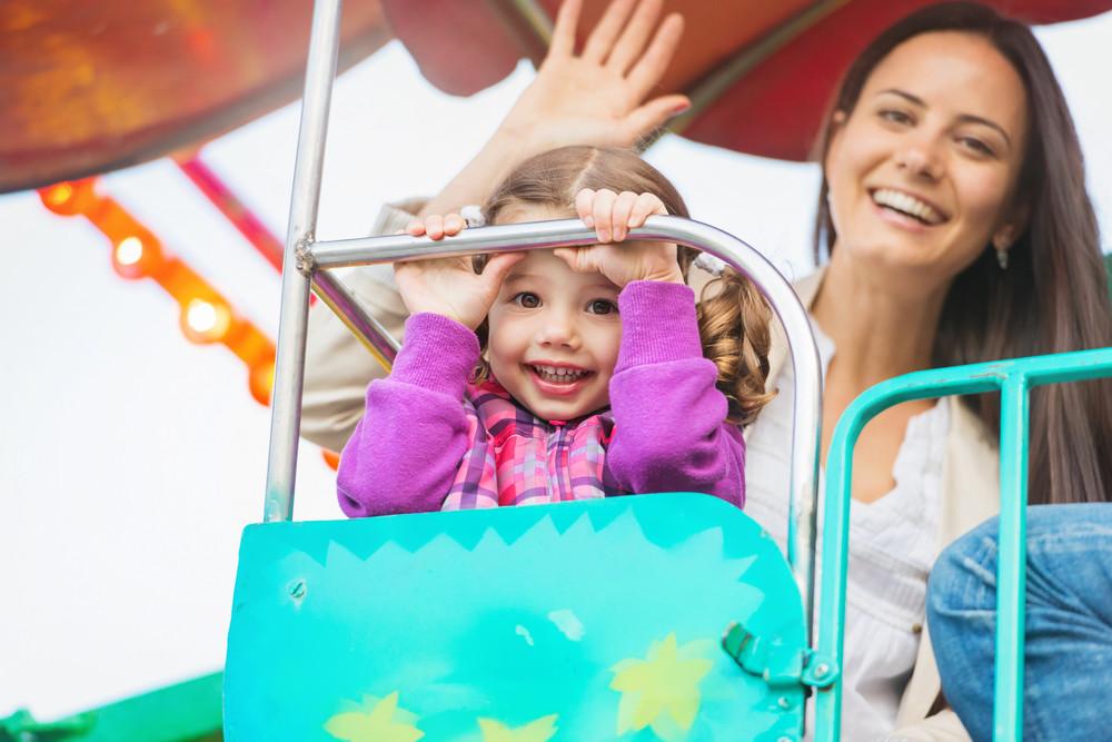 Cute little girl with her mother enjoying time at fun fair, amusement park