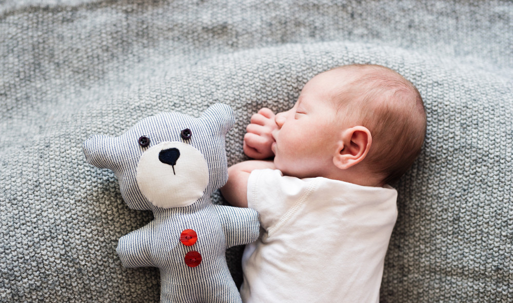 Cute Little Newborn Baby Boy Lying On Bed With His Teddy Bear