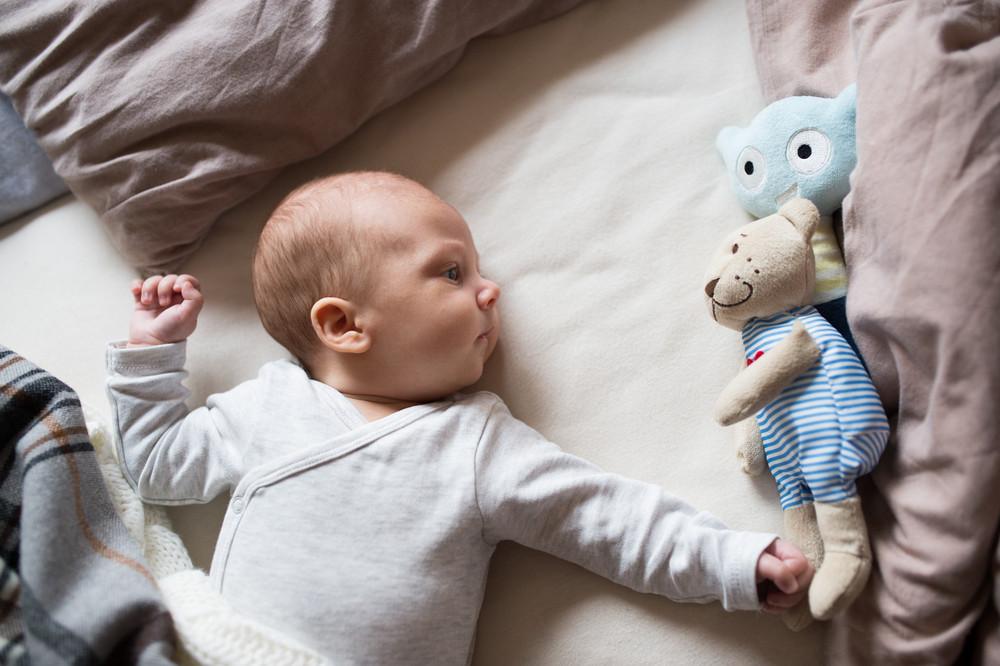 974d1e528 Cute newborn baby boy in gray onesie lying on bed, teddy bear toy next to