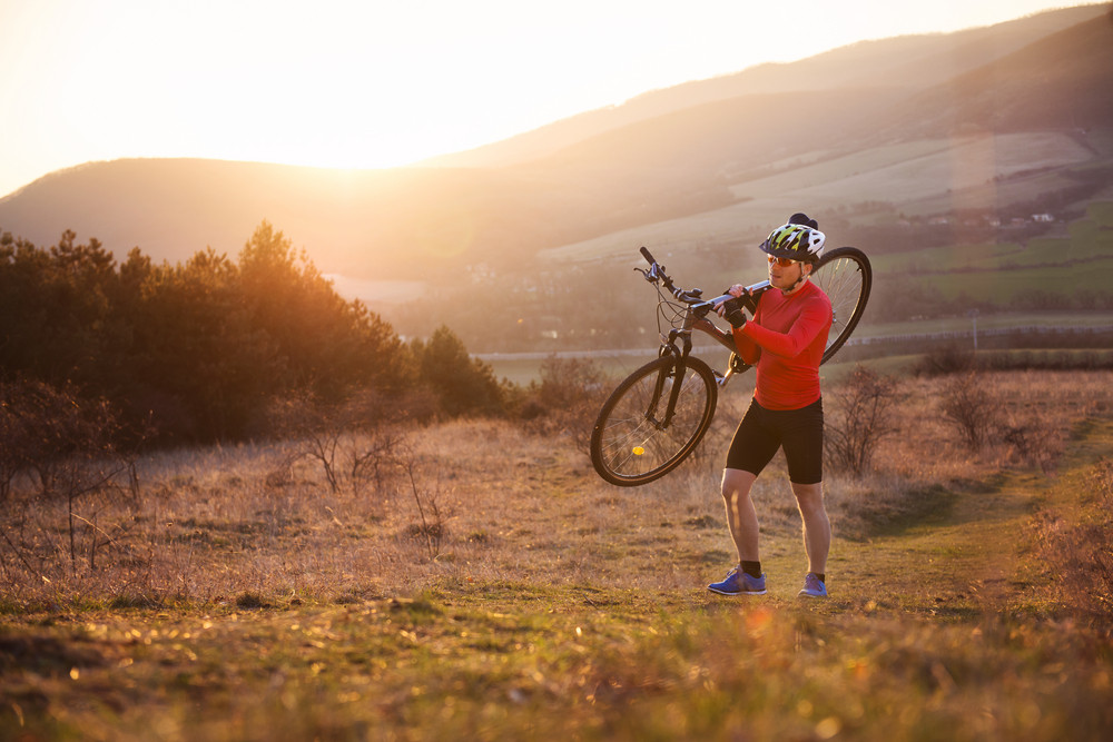 Cyclist man carrying his mountain bike on a sunny meadow