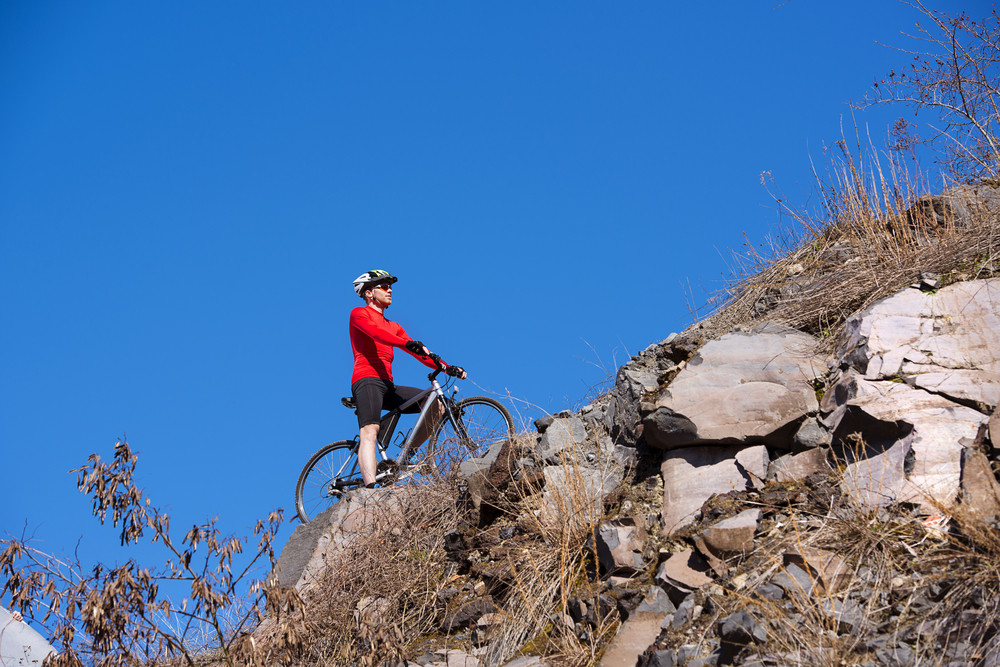Cyclist man riding a mountain bike along rocky mountain on a sunny day against a blue sky
