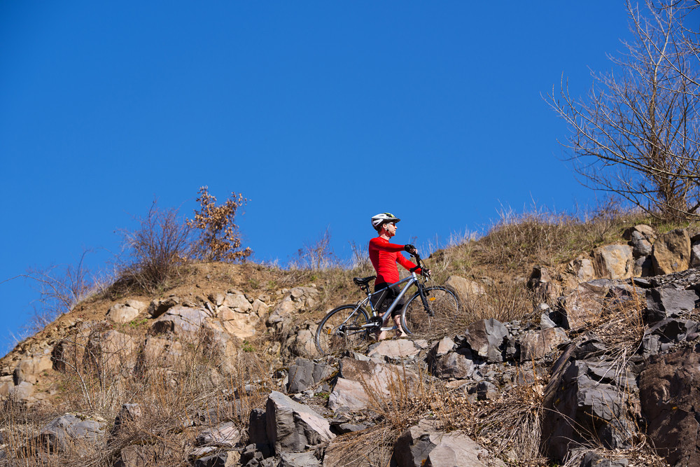 Cyclist man riding a mountain bike along rocky mountain on a sunny day against a blue sky