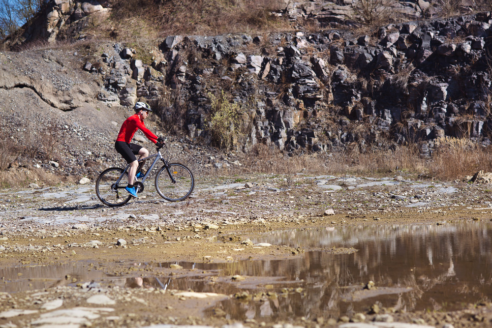 cyclist man riding mountain bike along the puddle in quarry