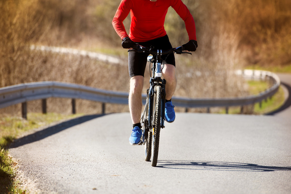 Cyclist man riding mountain bike on asphalt road Royalty-Free Stock