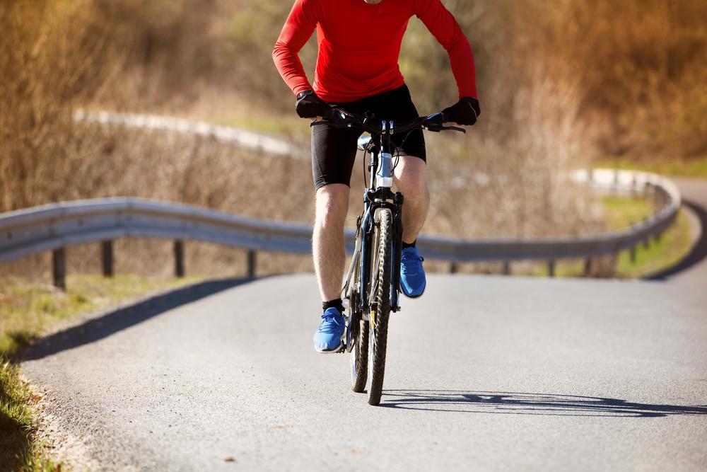 Cyclist man riding mountain bike on asphalt road