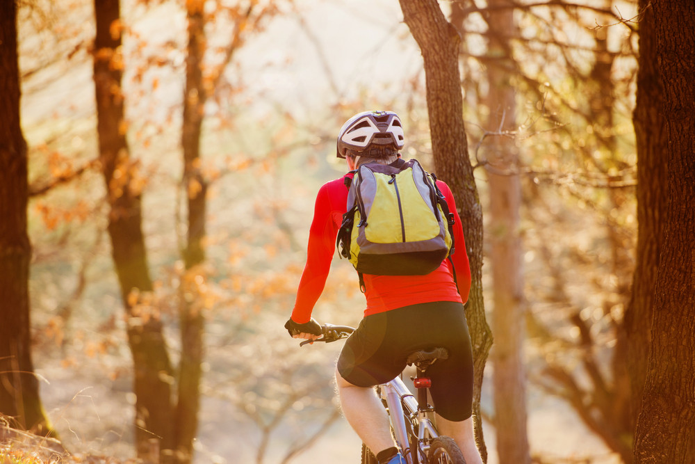 Cyclist man riding mountain bike on outdoor trail in autumn forest