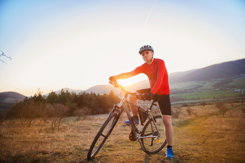 Cyclist man riding mountain bike on outdoor trail in sunny meadow