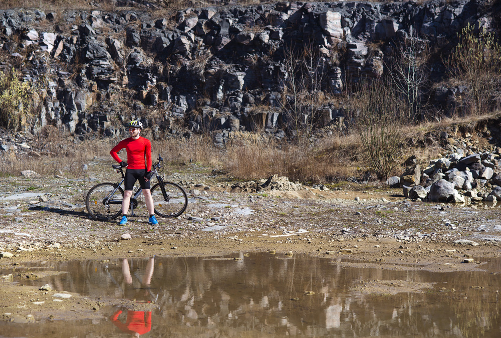cyclist man standing with his bike and reflecting in water puddle