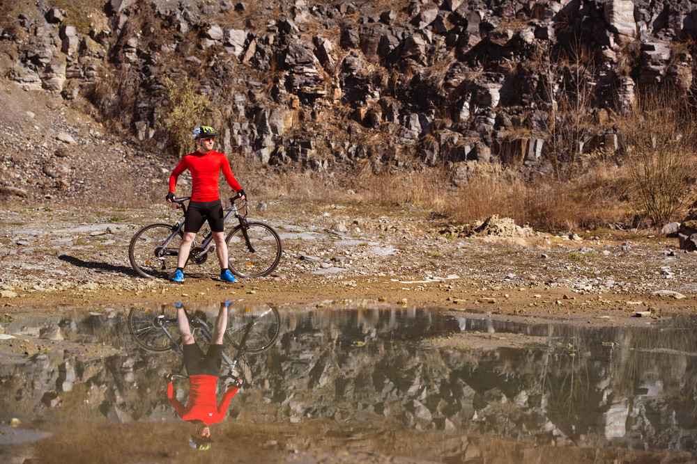 Cyclist man standing with his bike is reflecting in water puddle