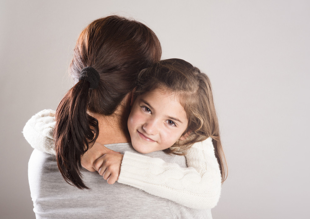 Daughter and mother are posing in studio