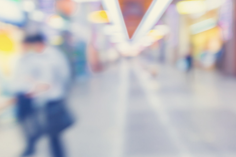 Defocused shopping mall interior with people walking in pastel colors