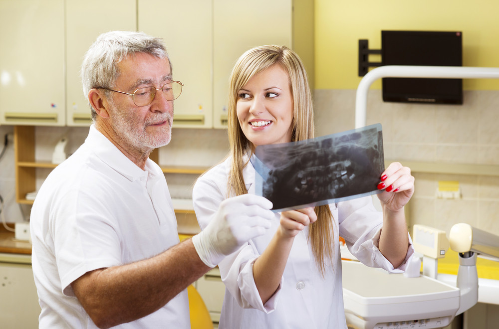 Dentist and his assistant are talking about patient's file