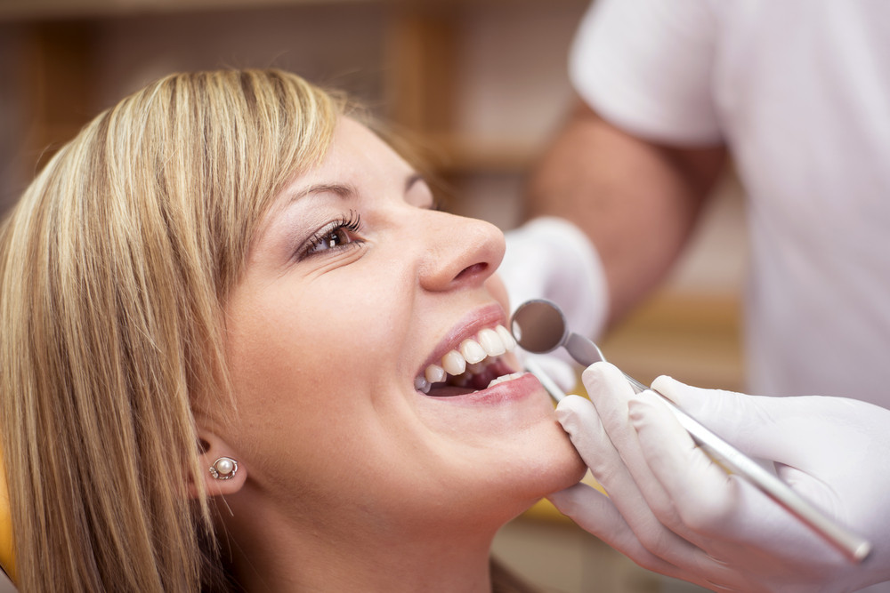 Dentist is doing treatment procedures in dental office.