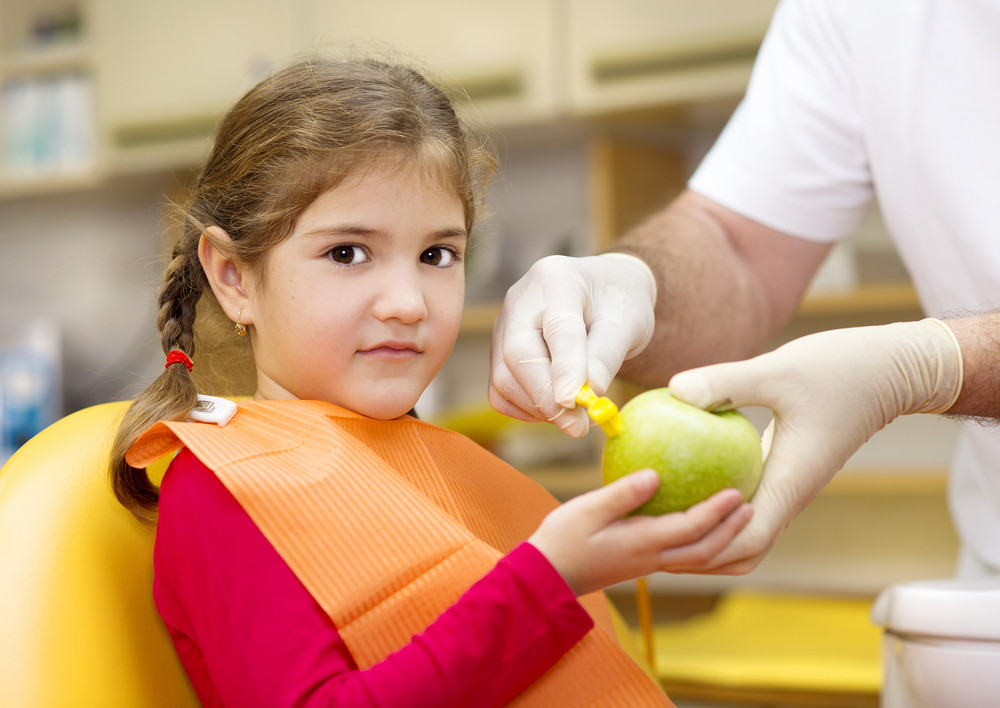 Dentist is showing the technique of teeth cleaning to a little girl