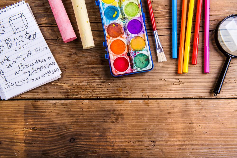 Desk with school supplies. Studio shot on wooden background.