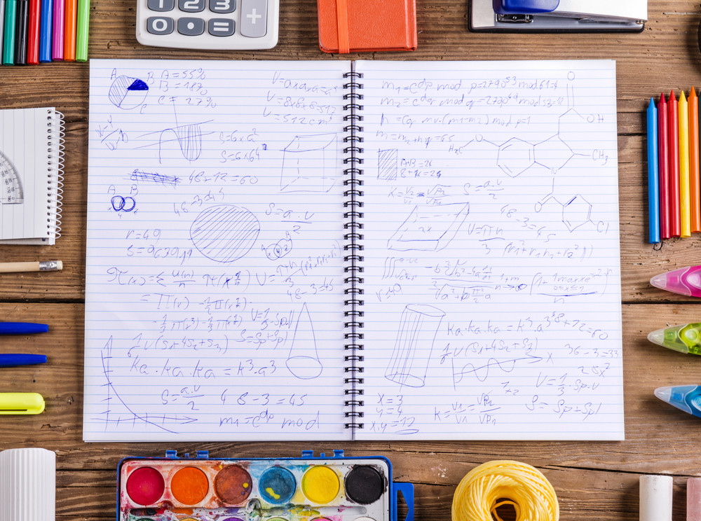 Desk with stationary and notebook with hand drawn doodles. Studio shot on wooden background.
