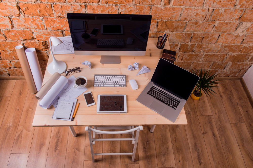 Desk with various gadgets and office supplies. Computer, smart phone, tablet and other devices and stationery around the workplace.