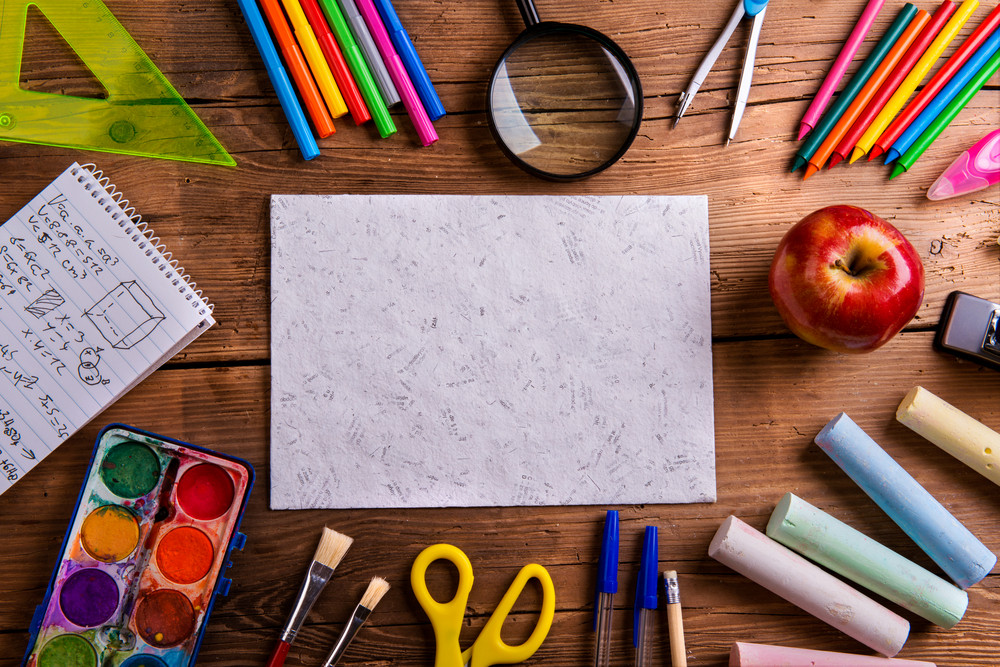 Desk with various school supplies and empty  sheet of paper  in the middle . Studio shot on wooden background, frame composition, empty copy space