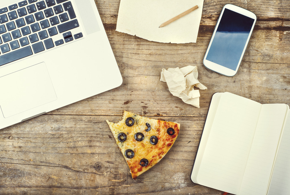 Desktop mix with office gadgets, supplies and pizza on a wooden office table background. View from above.