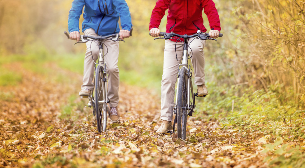Detail of active seniors legs riding bike in autumn nature. They relax outdoor.