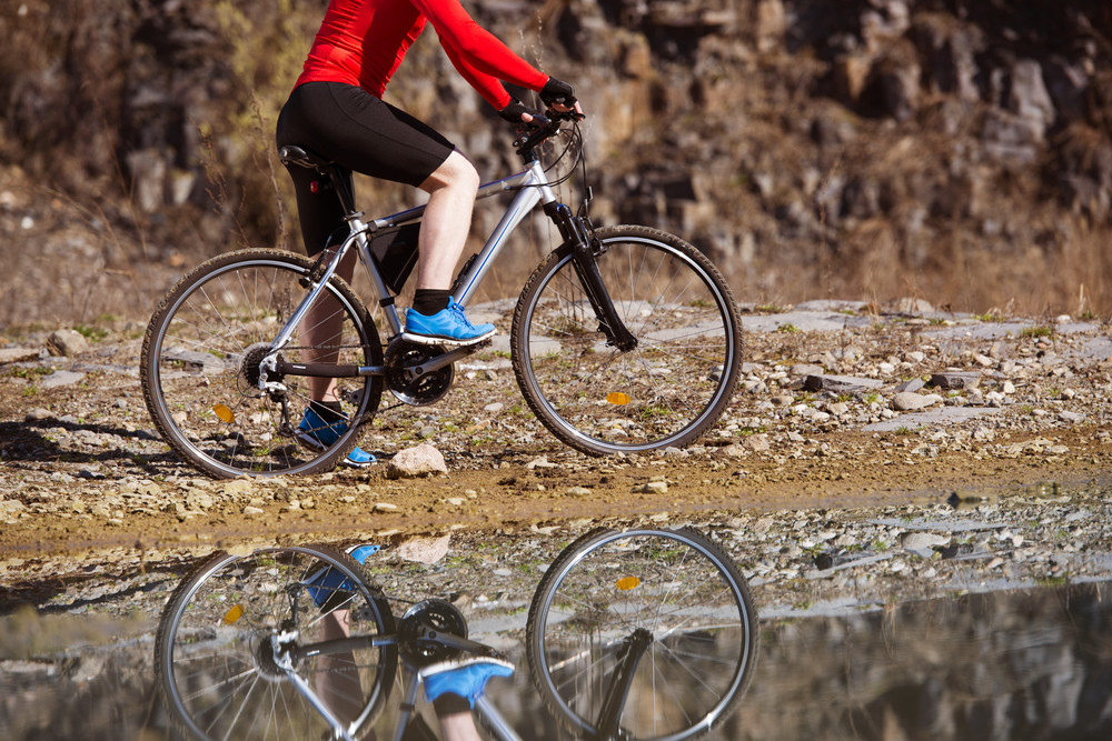 Detail of cyclist man reflecting in water puddle