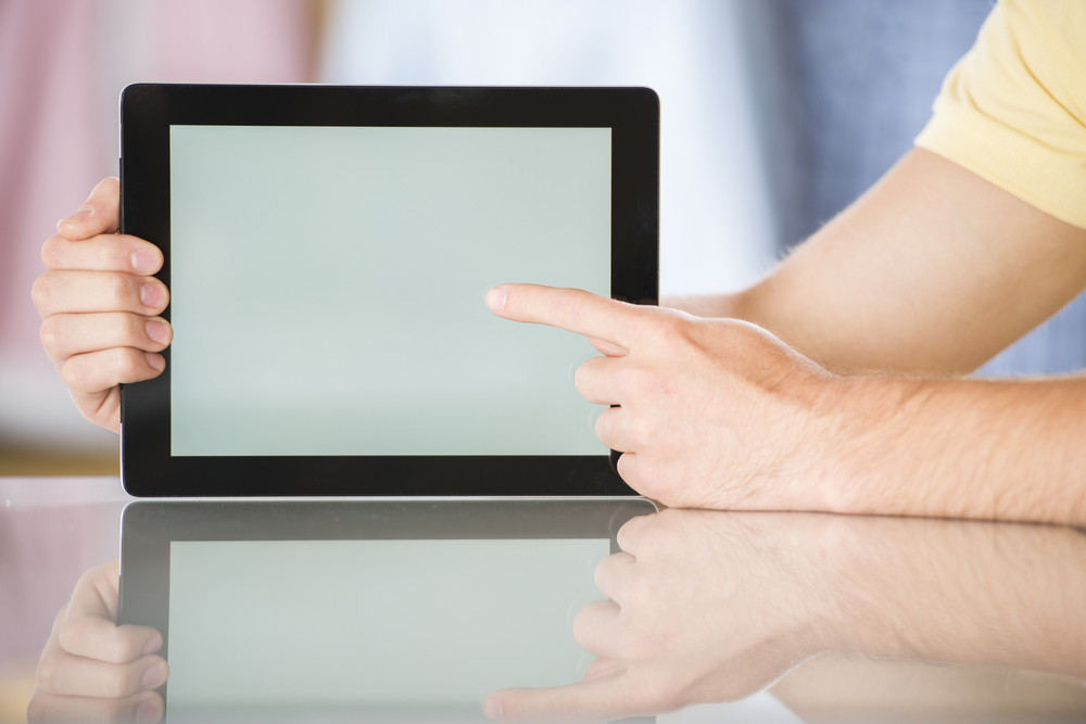 Detail of hands with tablet computer in studio